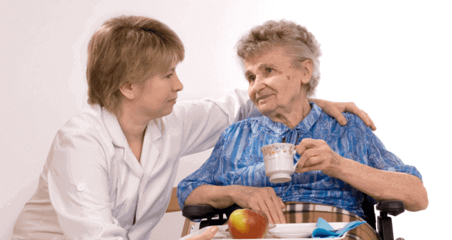 An elderly having a meal accompanied by a caregiver
