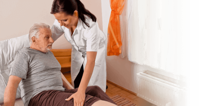 A caregiver assisting an elderly in bed