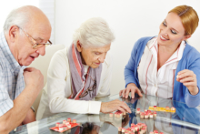 Elderly couple and a caregiver playing a game